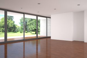 Empty modern living room with large window and parquet floor.